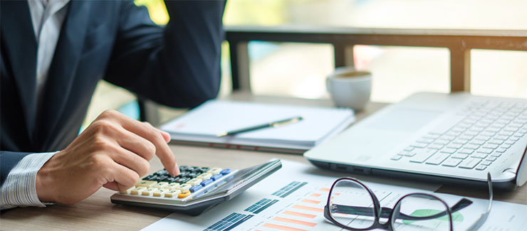 Establishing pay rates: Businessman using calculator for analysis