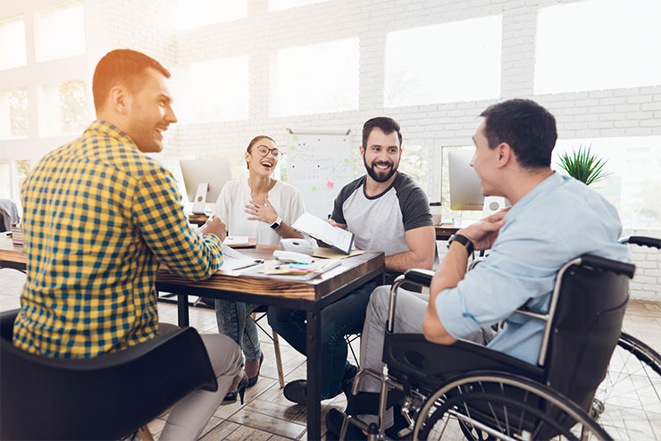 3 colleagues sit in chairs and 1 colleague sits in a wheelchair around a table at work