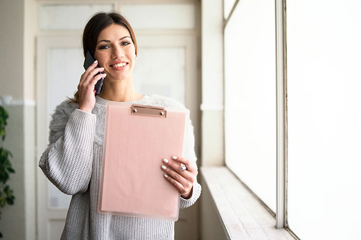 Question and Answer Examples for Phone Interviews: Young woman talking on the phone holding clipboard at work