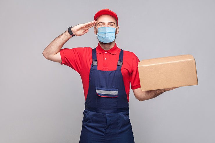 Re-opening work after COVID-19: Young man with surgical medical mask in blue uniform and red t-shirt standing, holding cardboard box on grey background