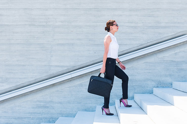 Business woman looking up ready to climb the success staircase
