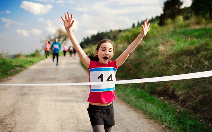 2020 date for International Women's Day: Young girl runner crossing finish line in a race competition in nature