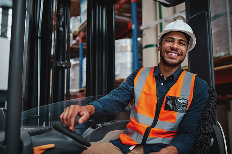Smiling worker operating forklift